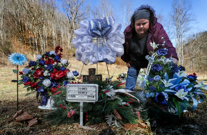 Brandy Stafford visits the grave of her brother, James Ramey, who is buried in a family cemetery just outside of Inez, Kentucky. Ramey died after contracting hepatitis A. Feb. 8, 2019
