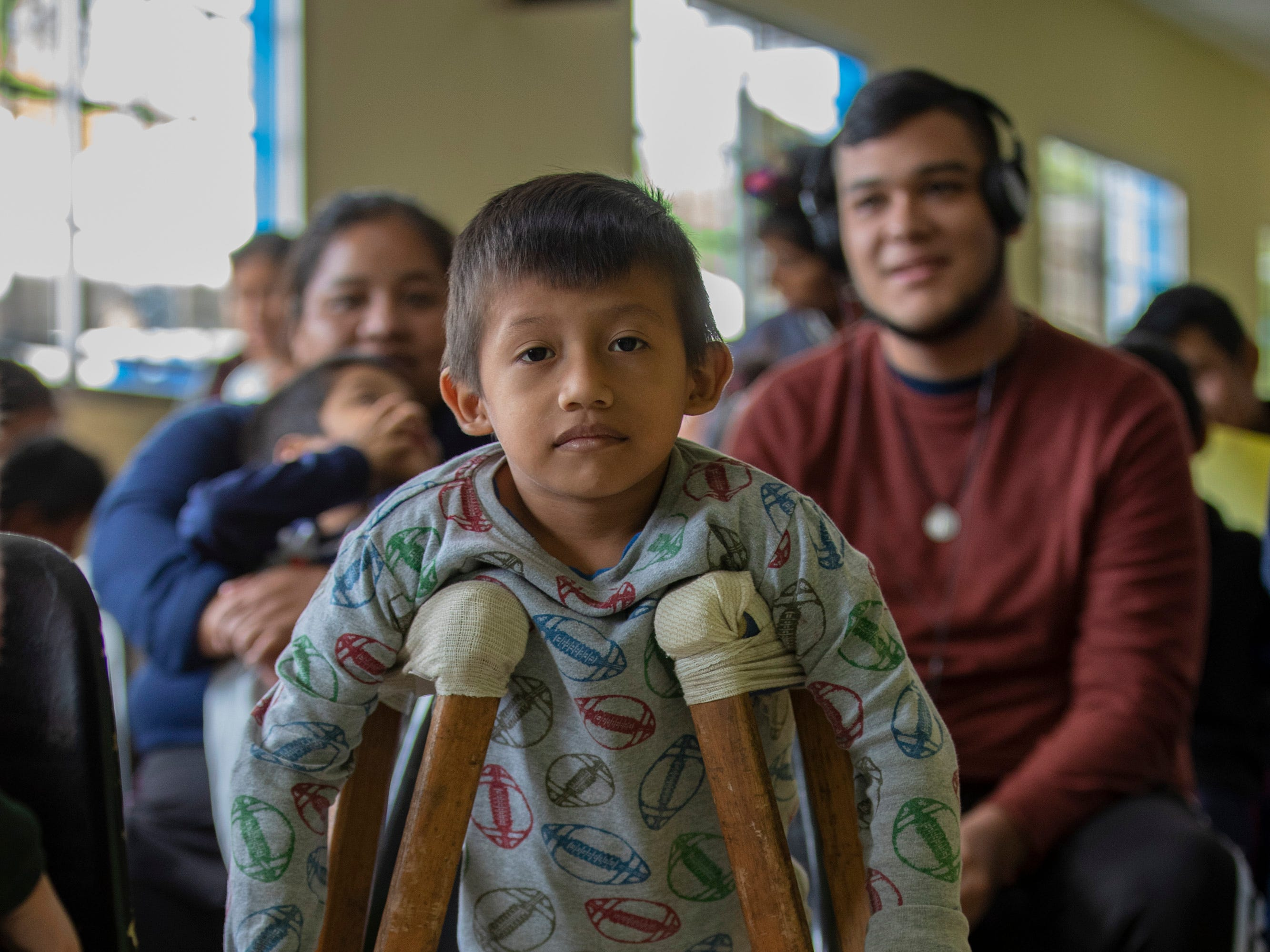 Angel Esthibon Kecinos Pedr, 7, waits with his homemade crutches in the lobby of the National Salama Hospital to see doctors about possible spine issues. Jan. 20, 2019
