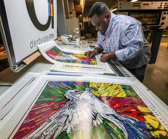 Chimel Ford takes a look at the finished poster.  Ford is the designer of the 2019 Kentucky Derby Festival poster that was unveiled today at Derby City Litho who is producing the posters.