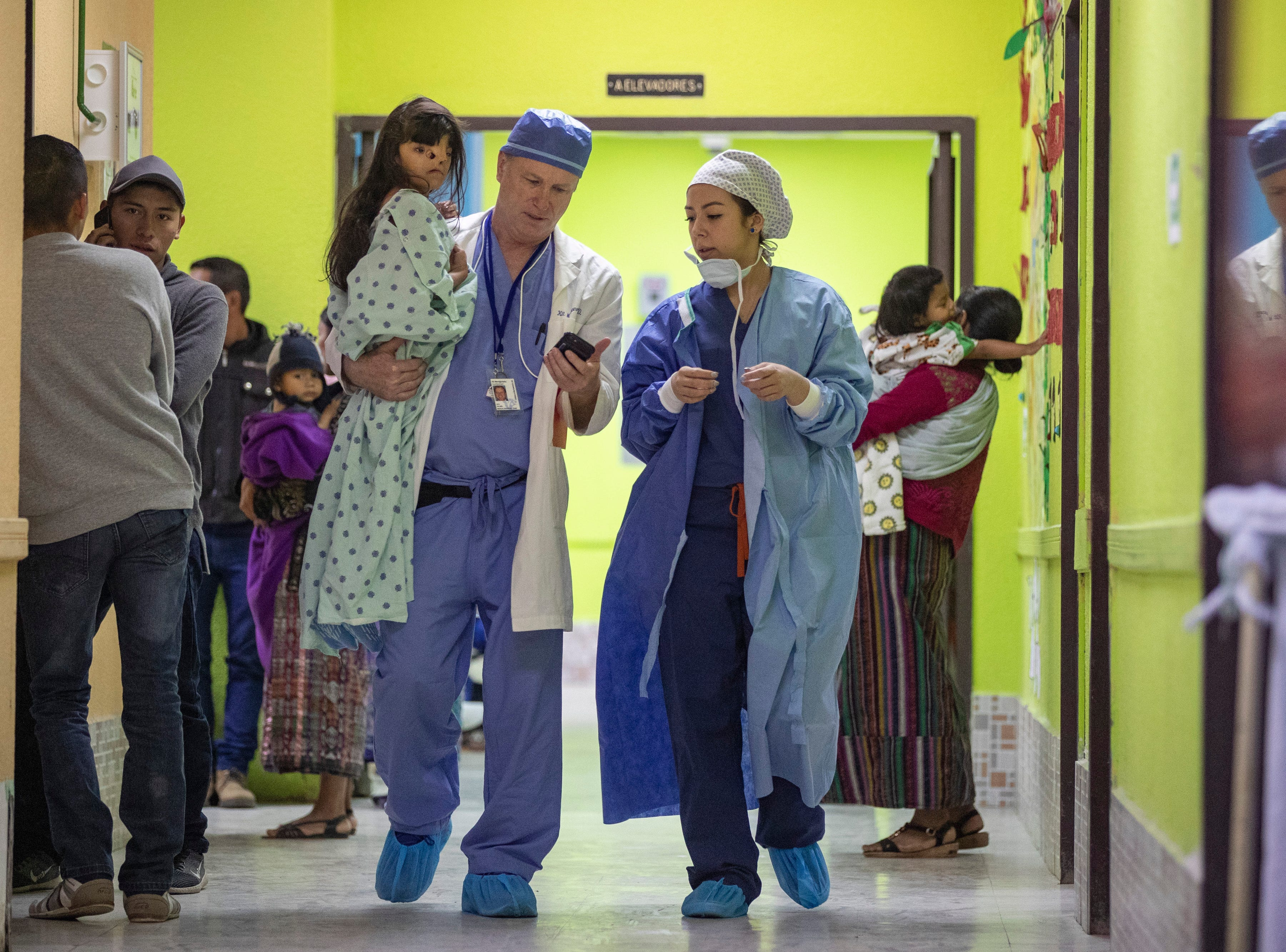Lexington, Kentucky's Shriner's Hospitals' director of anesthesia, Dr. Kit Montgomery, left, carries Evany Puac, 6, to receive her second plastic surgery to reconstruct her face after being born with a severe facial bilateral cleft as Brooklyn's Midtown Surgery Center's Jessica Parra looks on. Jan. 22, 2019