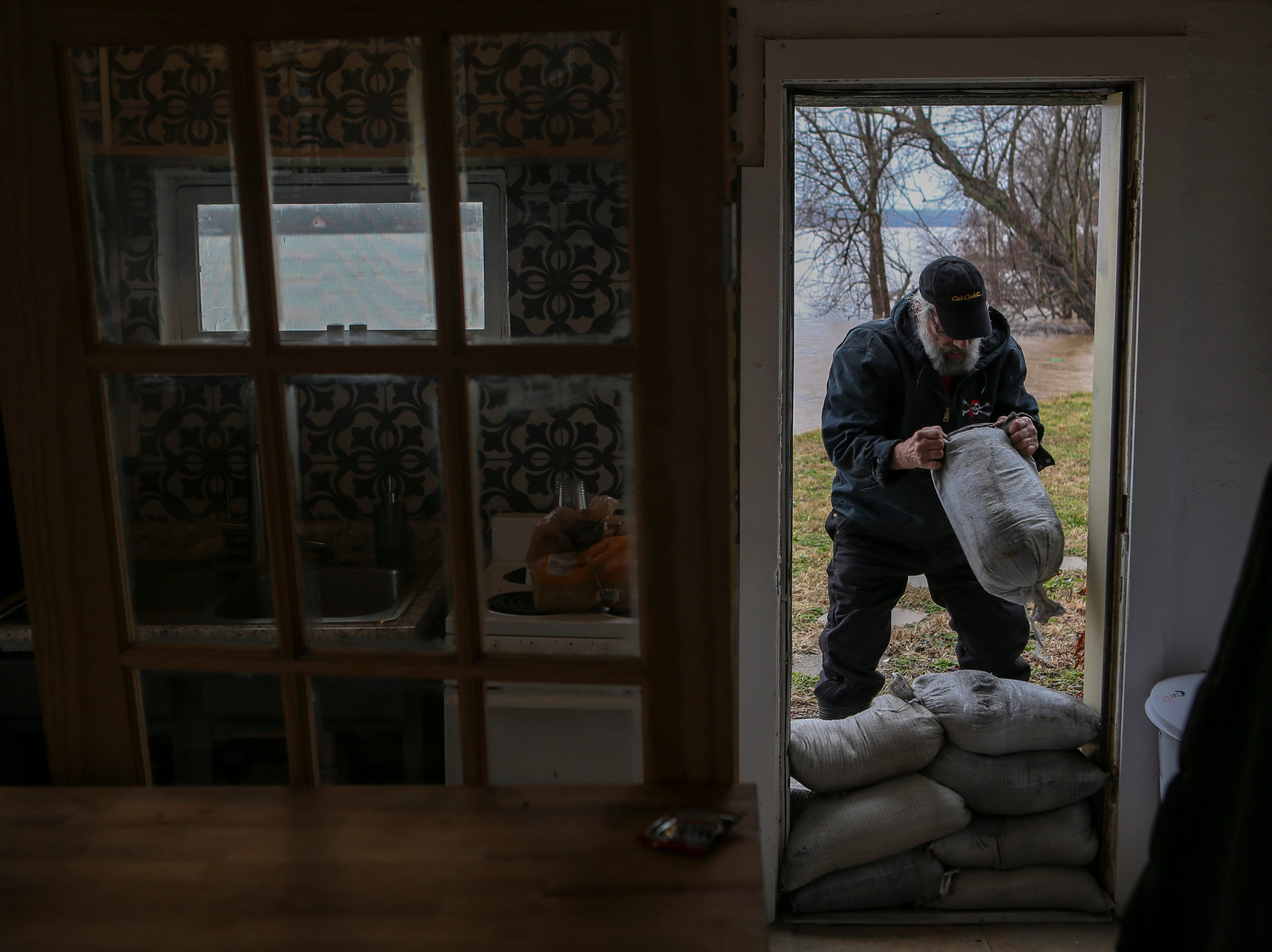 Tony Watterson stacks sandbags in a home's doorway in Utica, Ind. on Monday as the area braces for high river waters and flooding. Feb. 11, 2019