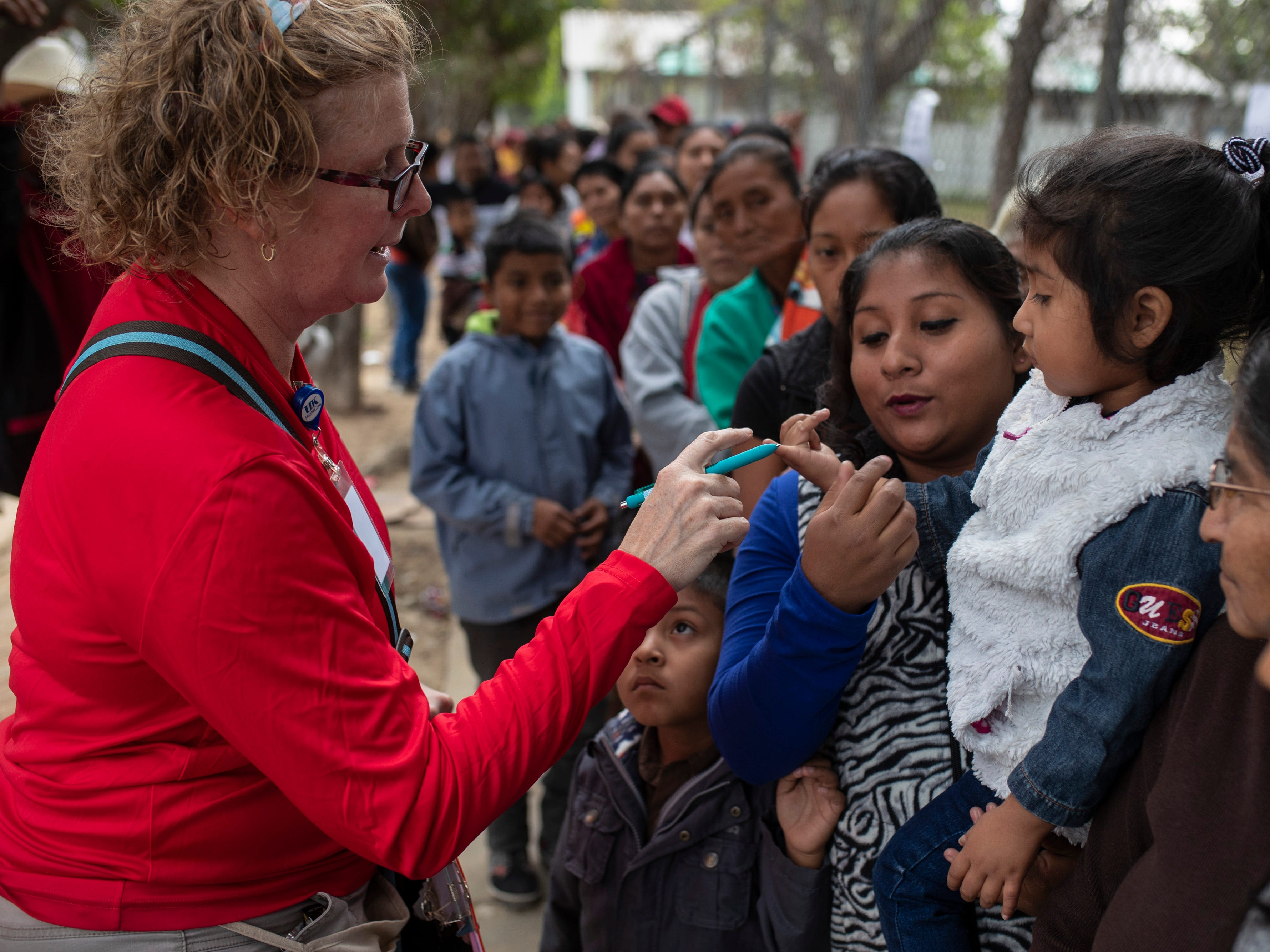 COTA board president Jennifer Christmann makes her way down the long line of hopeful patients outside the Hospital Nacional de Salamá on the first day of the medical mission. Christmann aims to help move those most in need of surgery up in the line to ensure as many are helped as possible. Jan. 20, 2019
