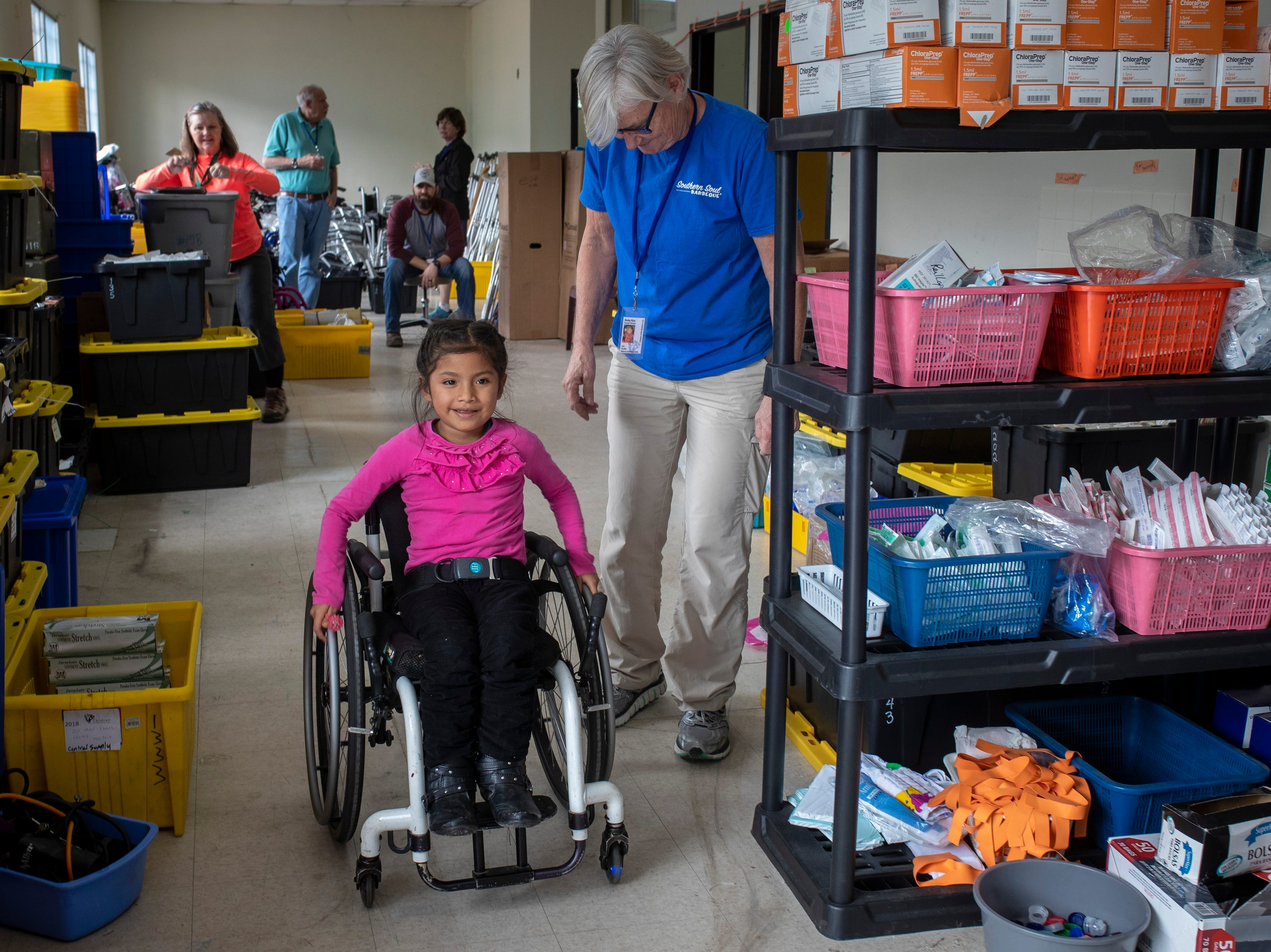Suleimy Solima Garcia, 7, diagnosed with spina bifida, tries out her brand new wheelchair in the COTA storage area as physical therapist Shelley Ryan of Lexington, Kentucky looks on. Jan. 21, 2019
