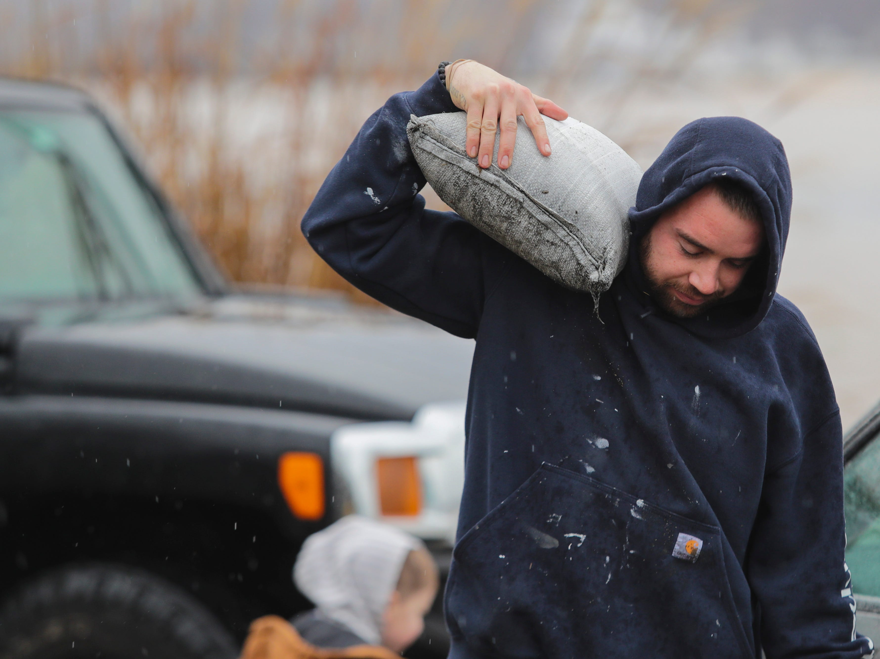 Chase Johnson loads sandbags into a property in Utica, Ind. as Ohio River water levels begin to rise. Feb. 11, 2019