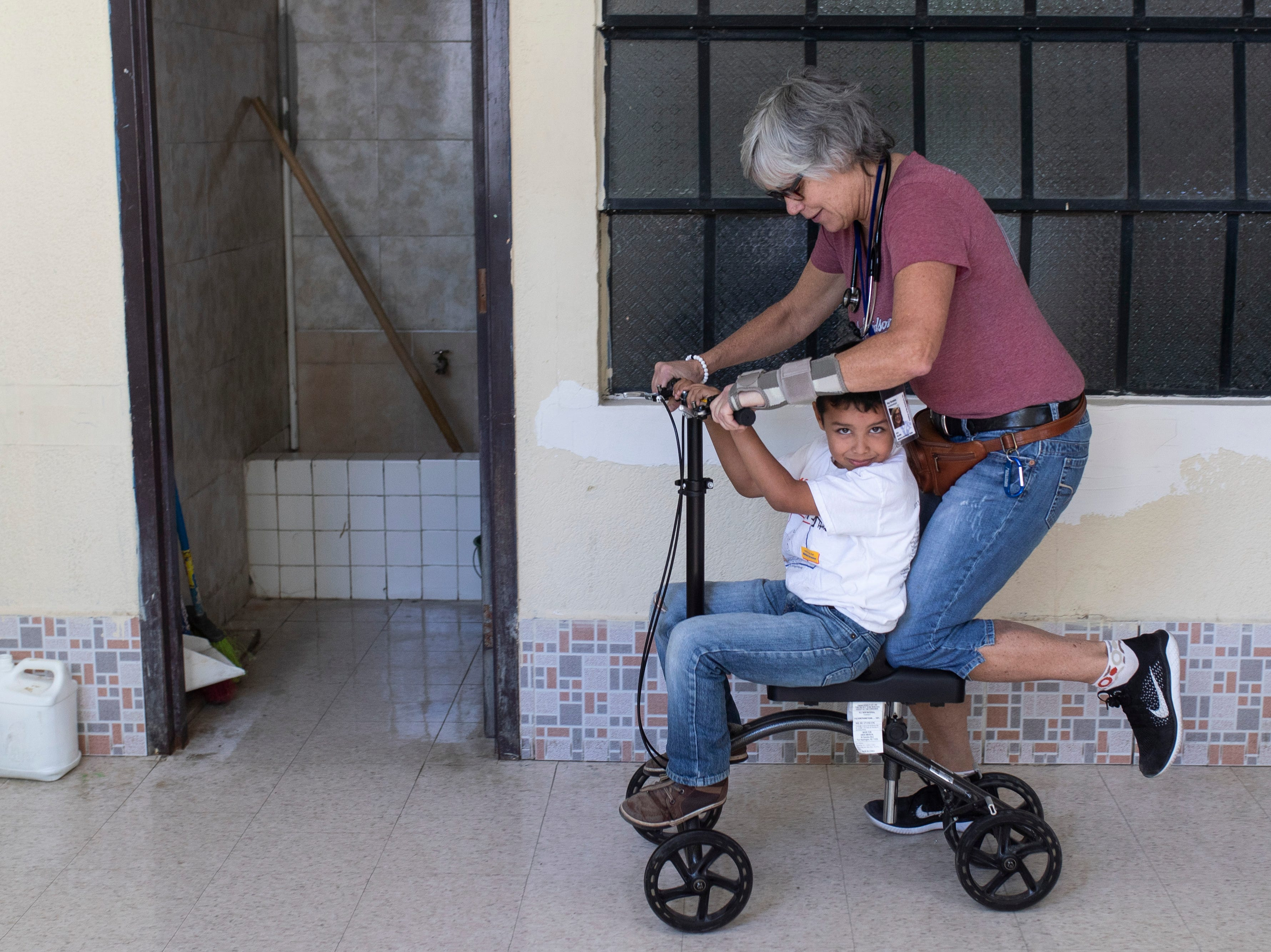 COTA vanesthesiologist Kay Beatty gives a patient a ride on her rehab scooter during the medical mission. Jan. 22, 2019
