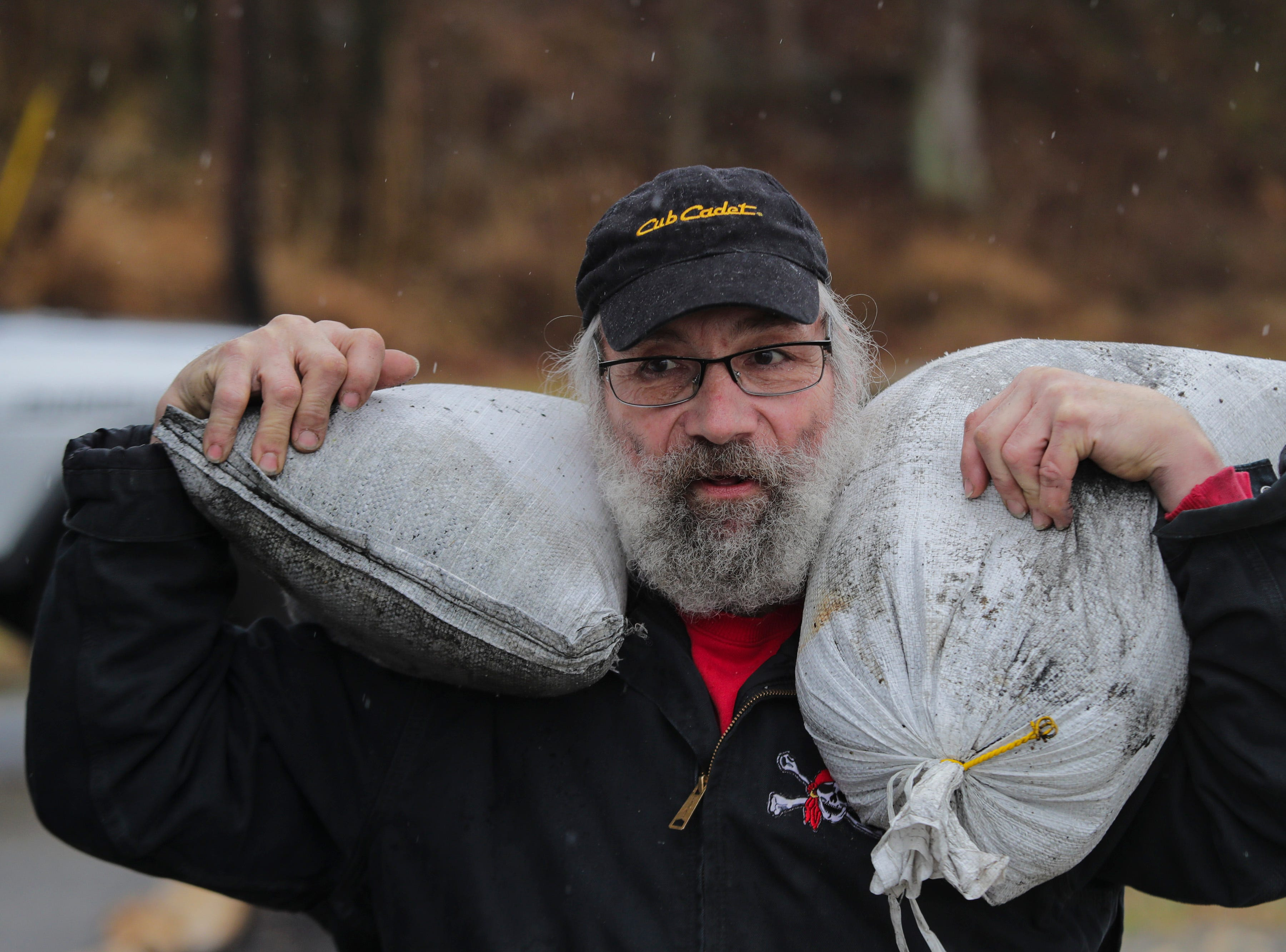 Tony Watterson carries two sandbags into a home in Utica, Ind. as Ohio River water levels begin to rise. Feb. 11, 2019