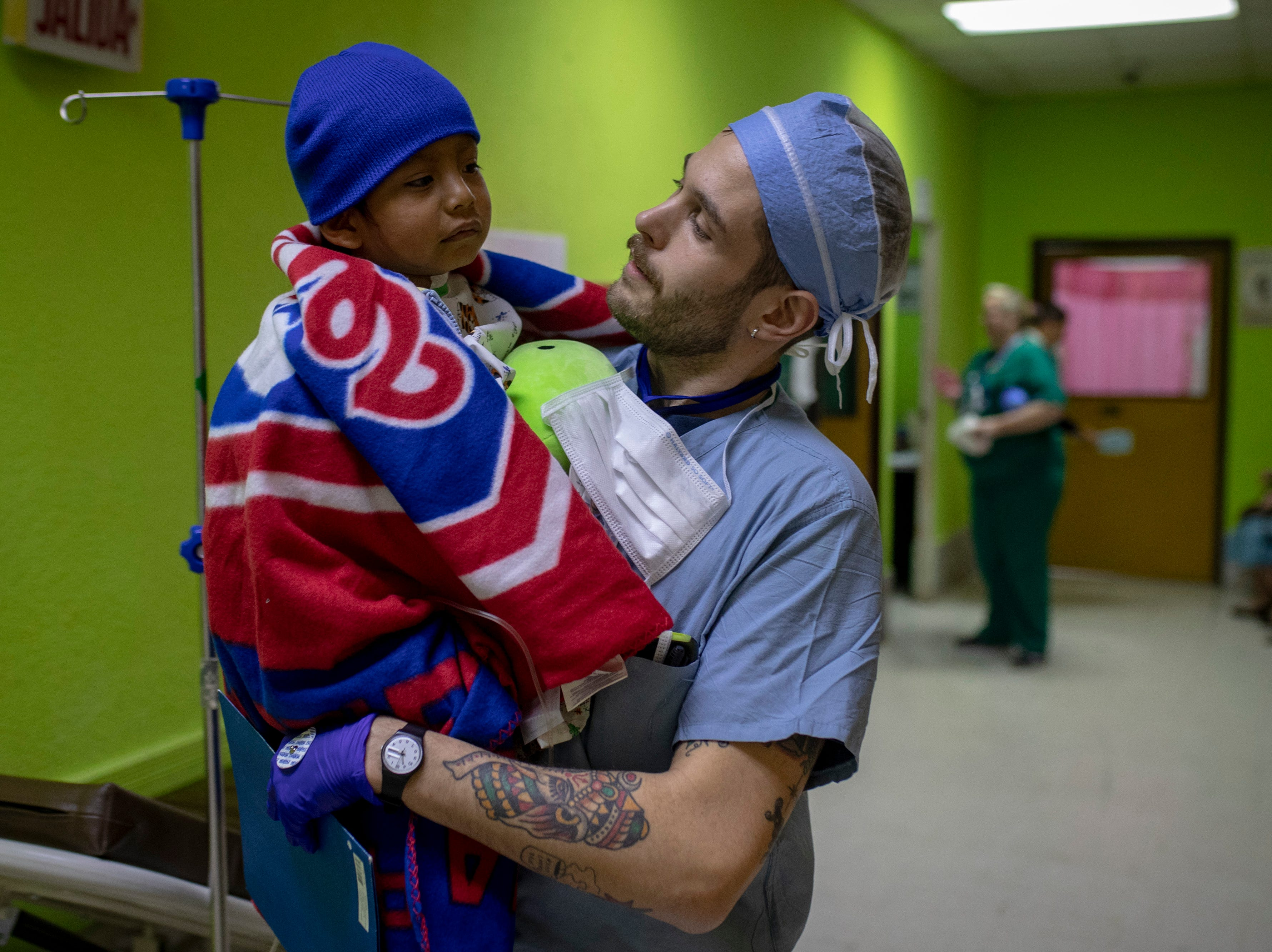 Fernando Damien Ixocopal Garcia, 5, is carried by COTA PACU nurse James Smith of Philadelphia to the children's recovery area following his surgery. Jan. 21, 2019