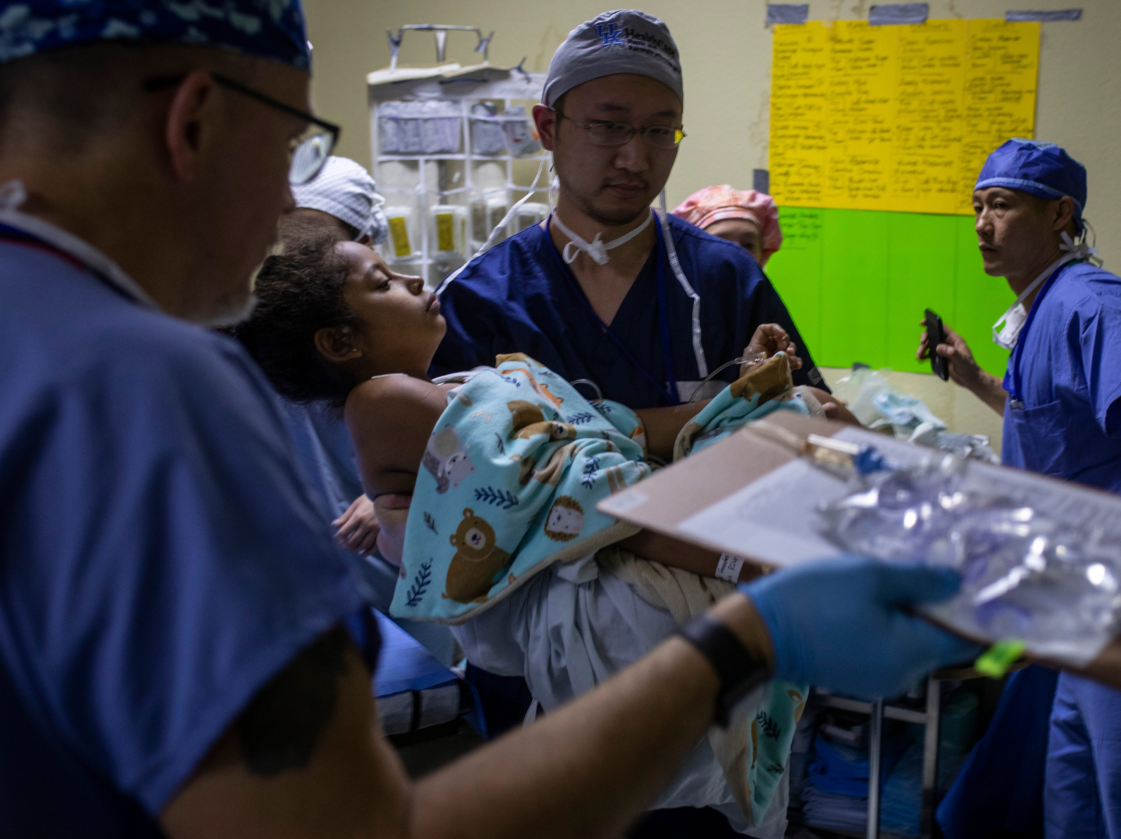 UK Hospital plastic surgery resident Duane Wang, center, carries Marangel Guadalupe Marroquin Rivera, 10, after she had a mass removed from her neck during the COTA 2019 medical mission to Salamá, Guatemala. Jan. 21, 2019