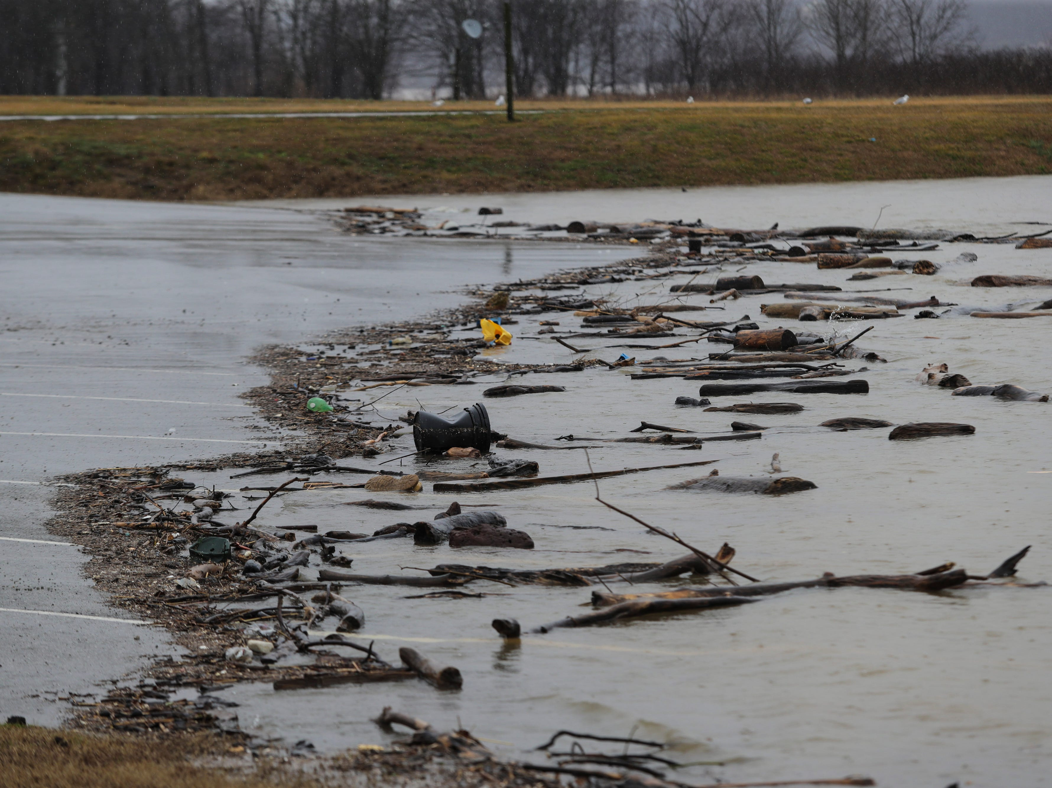 Debris and high waters move in to parking lots in Utica, Ind. as Ohio River water levels begin to rise. Feb. 11, 2019