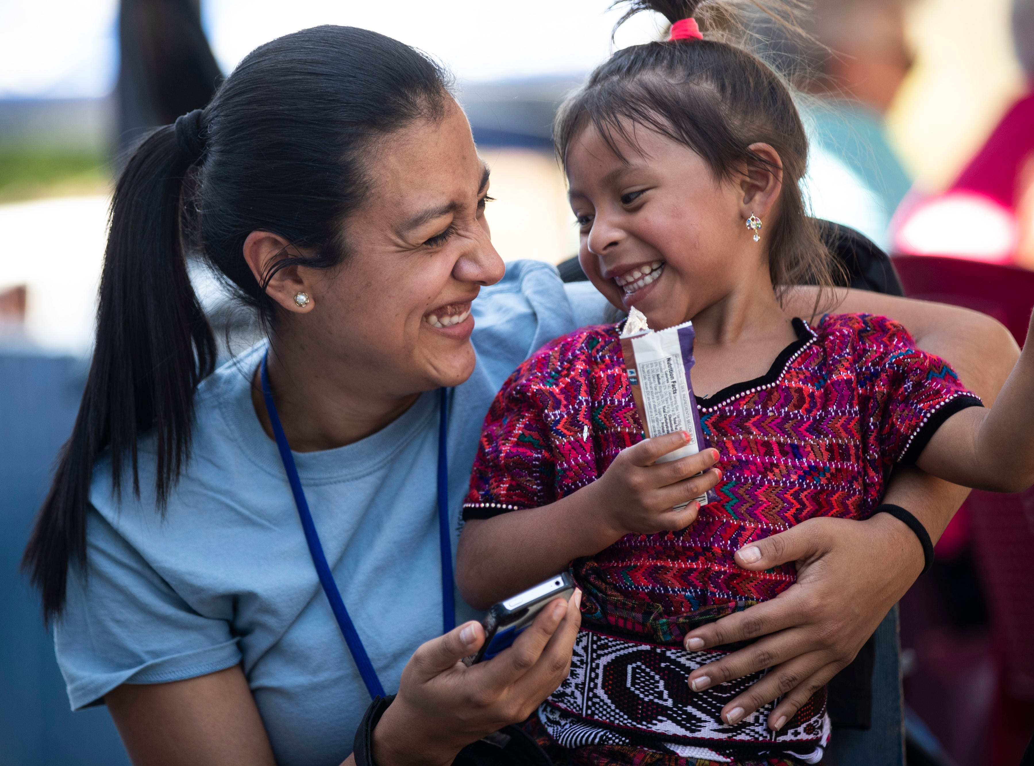 COTA volunteer and former COTA patient Heidy Fernandez, left, has a laugh with a waiting patient outside at Hospital Nacional de Salamá. Jan. 22, 2019