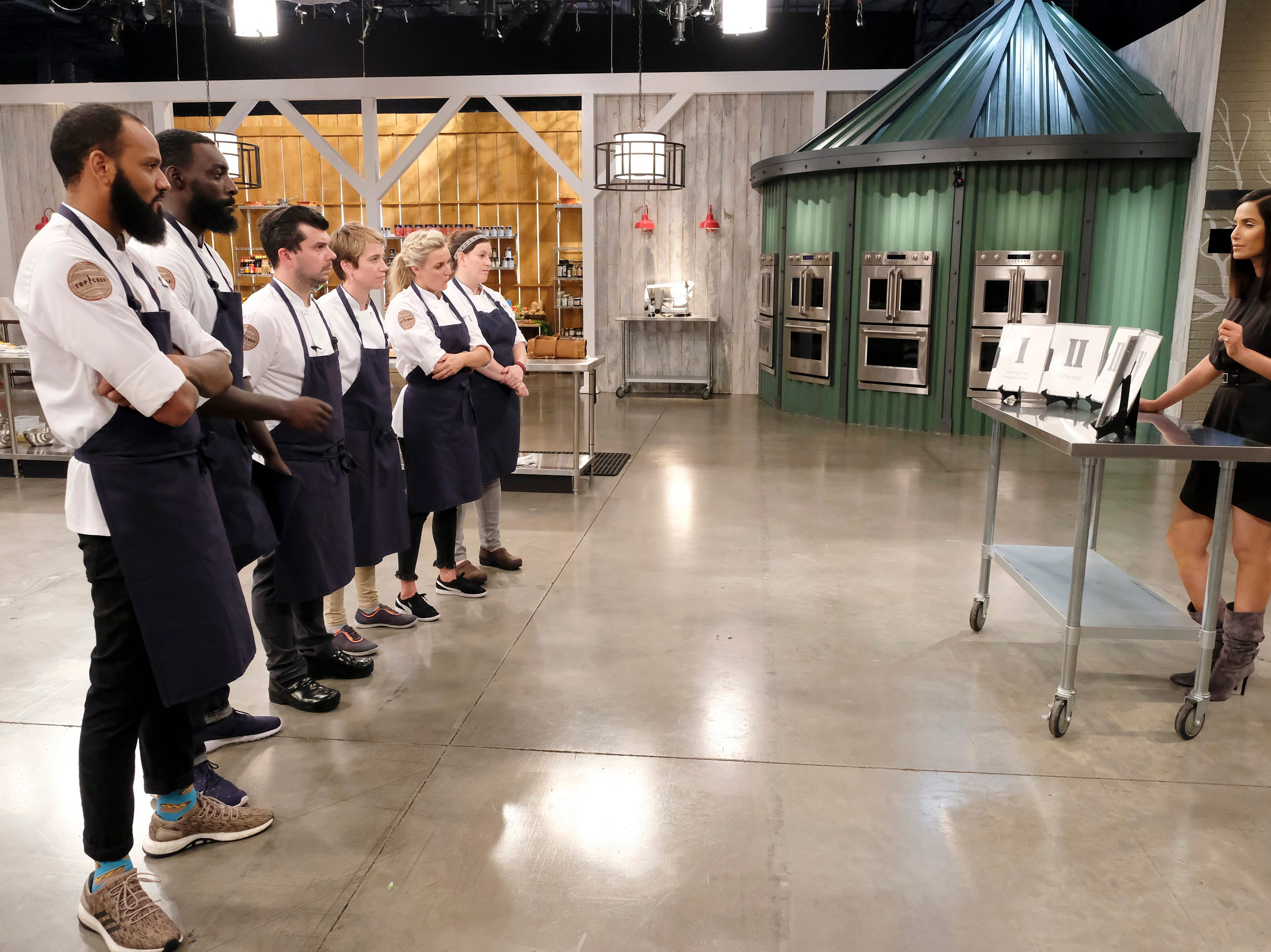 (From left to right): Contestants  Justin Sutherland, Eric Adjepong, Eddie Konrad, Adrienne Wright, Kelsey Barnard and Sara Bradley get challenge instructions from host Padma Lakshmi on episode 11 of Bravo's 'Top Chef:' Kentucky season.