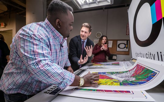 Chimel Ford takes a look at the finished poster with sales rep. Steve Liesinger.  Ford is the designer of the 2019 Kentucky Derby Festival poster that was unveiled today at Derby City Litho who is producing the posters.