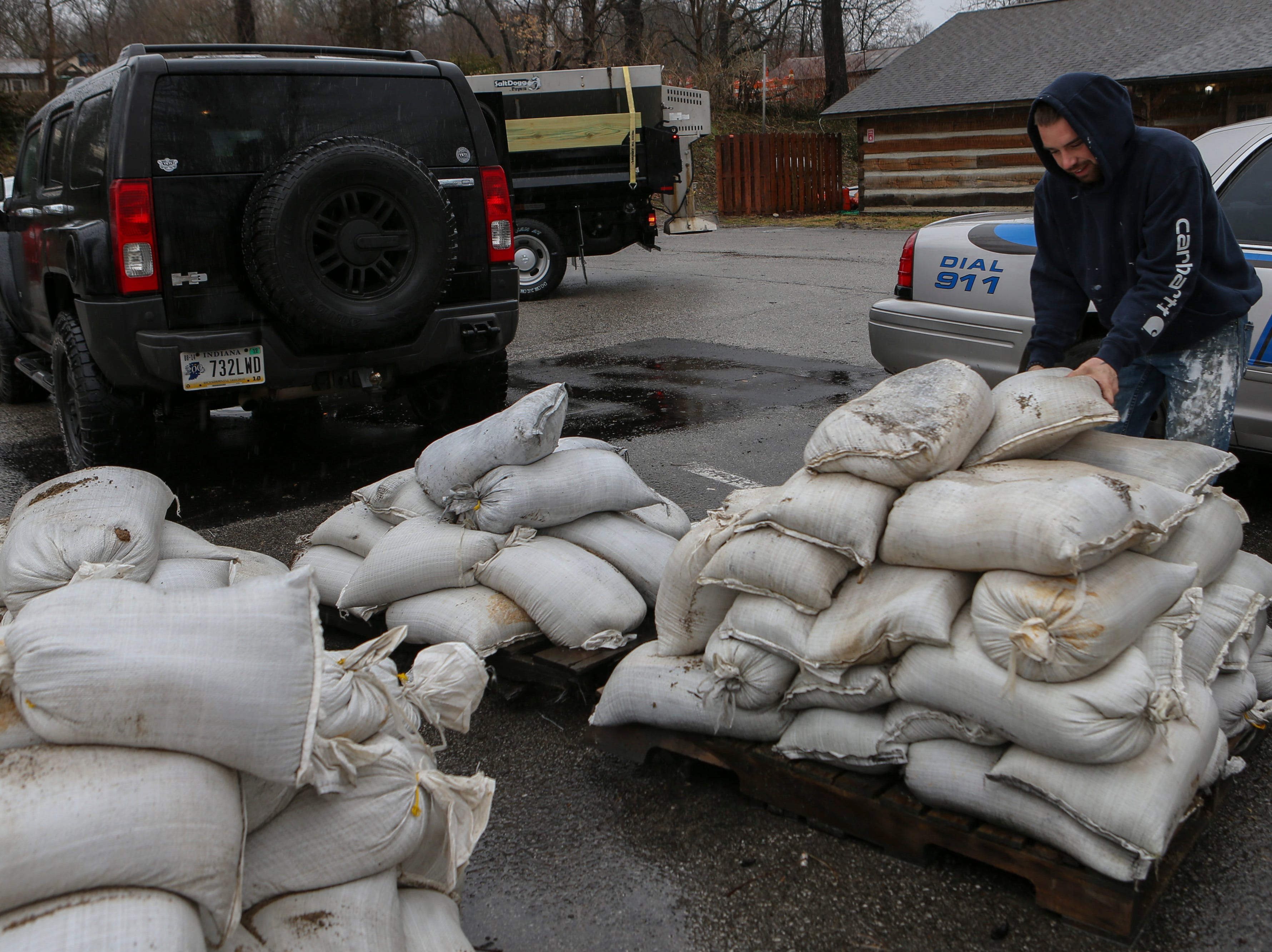 Chase Johnson picks up sandbags in Utica, Ind. on Monday as the area braces for high river waters and flooding. Feb. 11, 2019