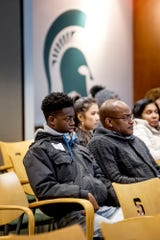 Andrew Johnson, 17, left, of Zion, Illinois, and his father Maurice, listen during a presentation before a walking tour of the campus for prospective students on Friday, Feb. 8, 2019, in East Lansing.