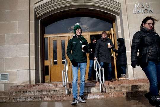 High school junior Aidan Svoboda, left, of Austin, Texas, along with other prospective students leave the MSU Union during a walking tour of the Michigan State University campus led by student guides on Friday, Feb. 8, 2019, in East Lansing.