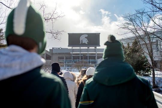 Prospective students and their parents make a stop outside Spartan Stadium during a walking tour of the Michigan State University campus on Friday, Feb. 8, 2019, in East Lansing.