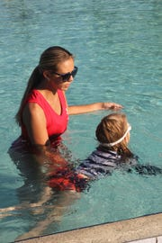 Aquatics program director Morgan Joseph works with a young learner swimmer at the Marco Y.