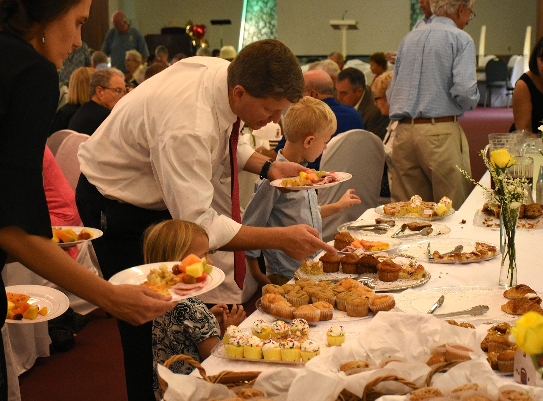 Pastor Mark Williams and his wife Emily, left, help their children Marie and Nolan pick out baked goods at the brunch following the dedication. United Church of Marco Island held a ceremony Sunday dedicating their newly erected steeple, which was damaged during Hurricane Irma.