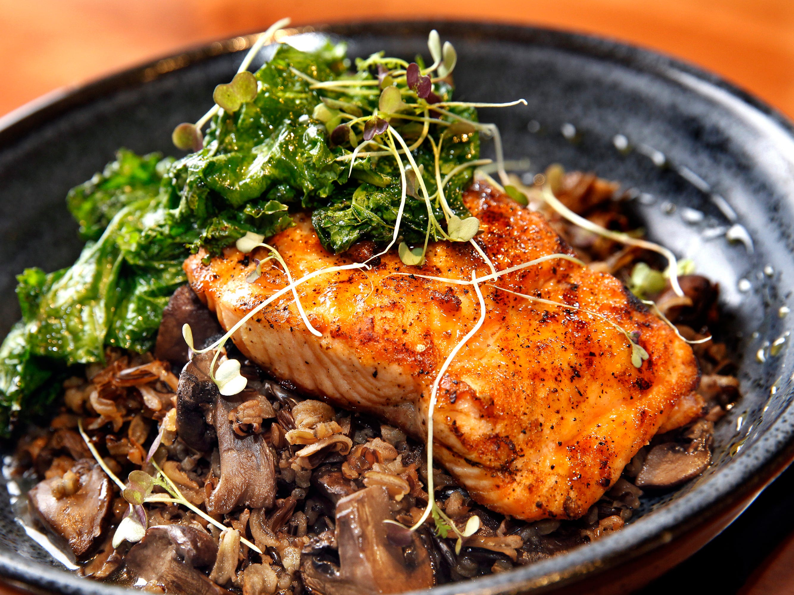 The Mapled-Glazed Atlantic Salmon served with roasted mushroom wild rice, wilted mustard greens and maple glaze from the Twisted Fire restaurant at 515 E. Wisconsin Ave., Oconomowac, Wi.