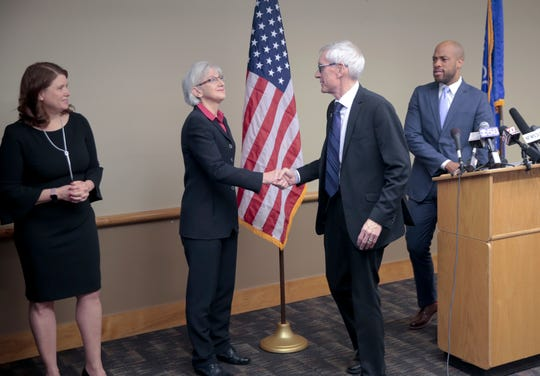 Democratic Gov-elect Toney Evers shakes hands with new Veterans Affairs secretary Mary Kolar after a press conference in which Evers announced two new cabinet secretaries, and his new budget director Friday Dec. 28, 2018 in Madison, Wisc. Kathy Blumenfeld, Department of Financial Institutions secretary is at left. Gov-elect Tony  Evers appointed Brian Pahnke new budget director, Blumenfeld, Department of Financial Institutions secretary, and Mary Kolar, a retired U.S. Navy captain as Veterans Affairs secretary.