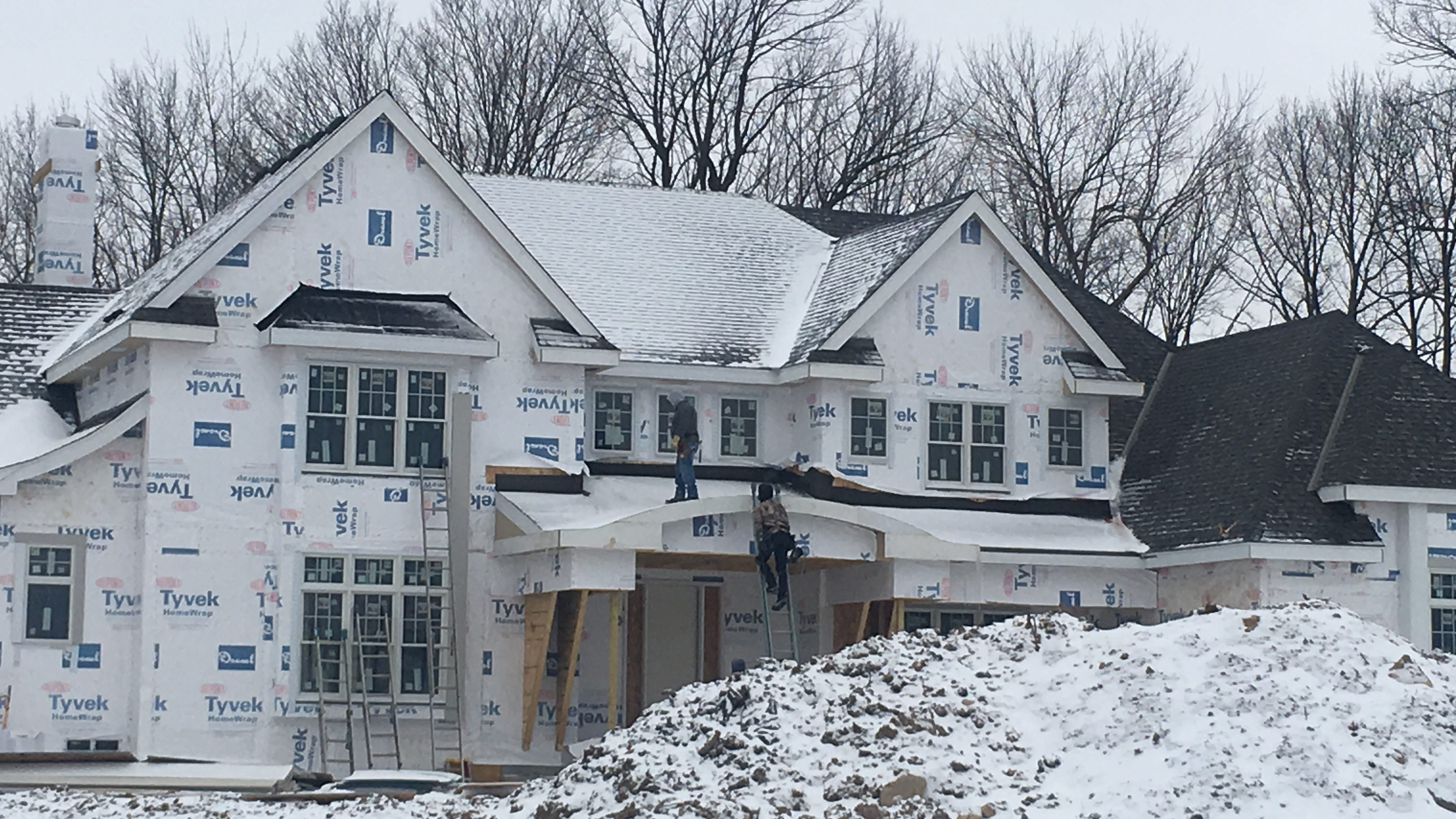 Crews work on a luxury home being constructed in...