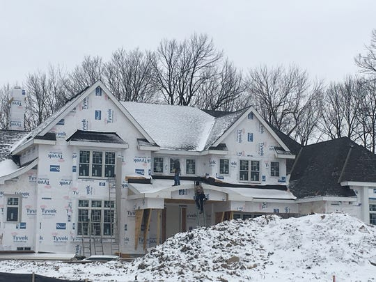 Crews work on a luxury home being constructed in Brookfield.