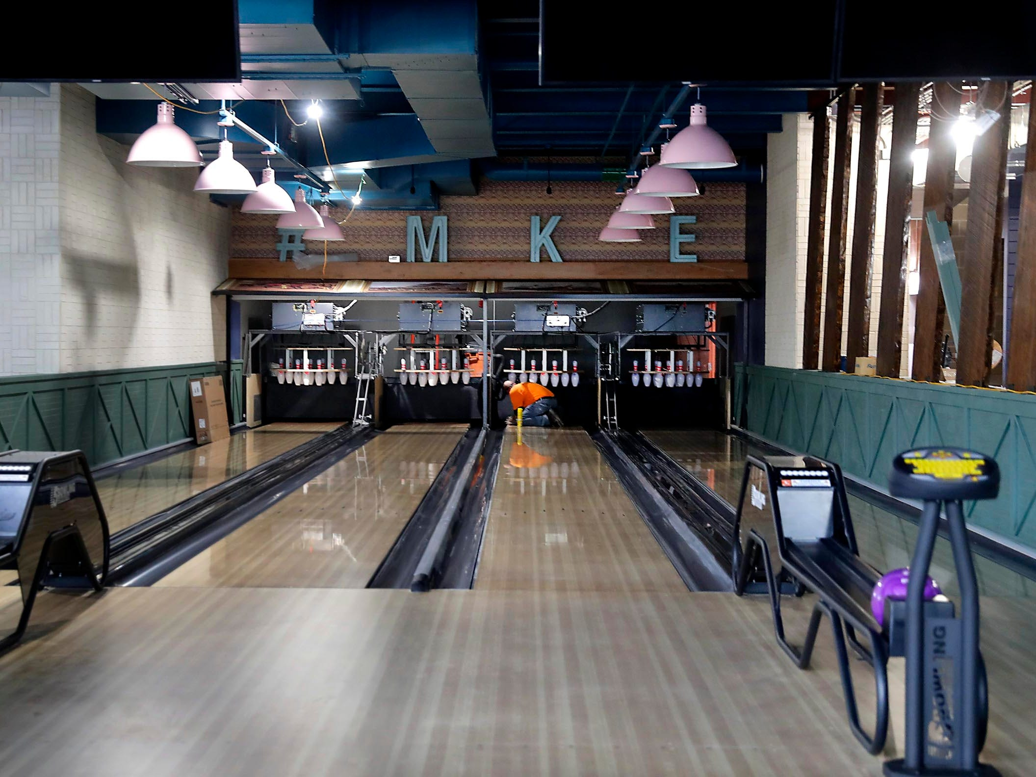 A worker works on a bowling lane Monday at Punch Bowl Social.
