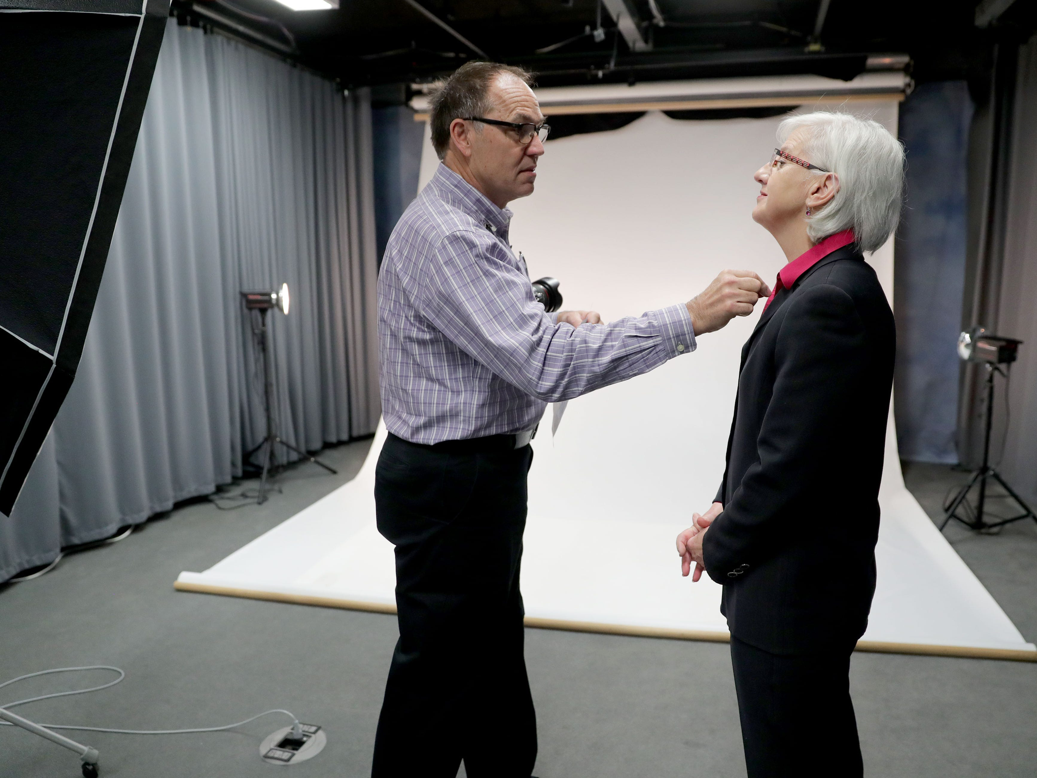 Photographer Eugene Russell removes a piece of lint from Wisconsin Department of Veterans Affairs Secretary-designee Mary M. Kolar before getting her photo taken at the Zablocki Veterans Affairs Medical Center in Milwaukee on Thursday, Jan. 17, 2019. The photo session was part of the The I Am Not Invisible project, that's been done in several states and made a stop at the VA Medical Center on Thursday. A photographer from Washington, D.C. captured portraits of female veterans of all branches, conflicts and age groups for a touring exhibit.