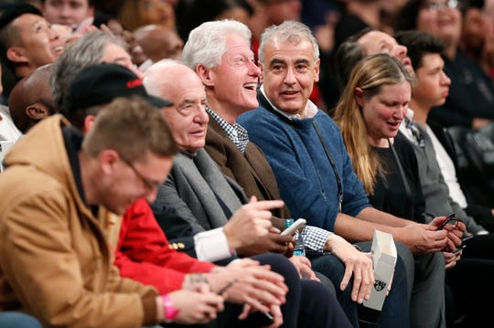 Bucks co-owner Marc Lasry (blue sweater) reacts as former President Bill Clinton smiles after seeing his image on a video screen above the court during a game between the Brooklyn Nets and Milwaukee on Feb. 4.