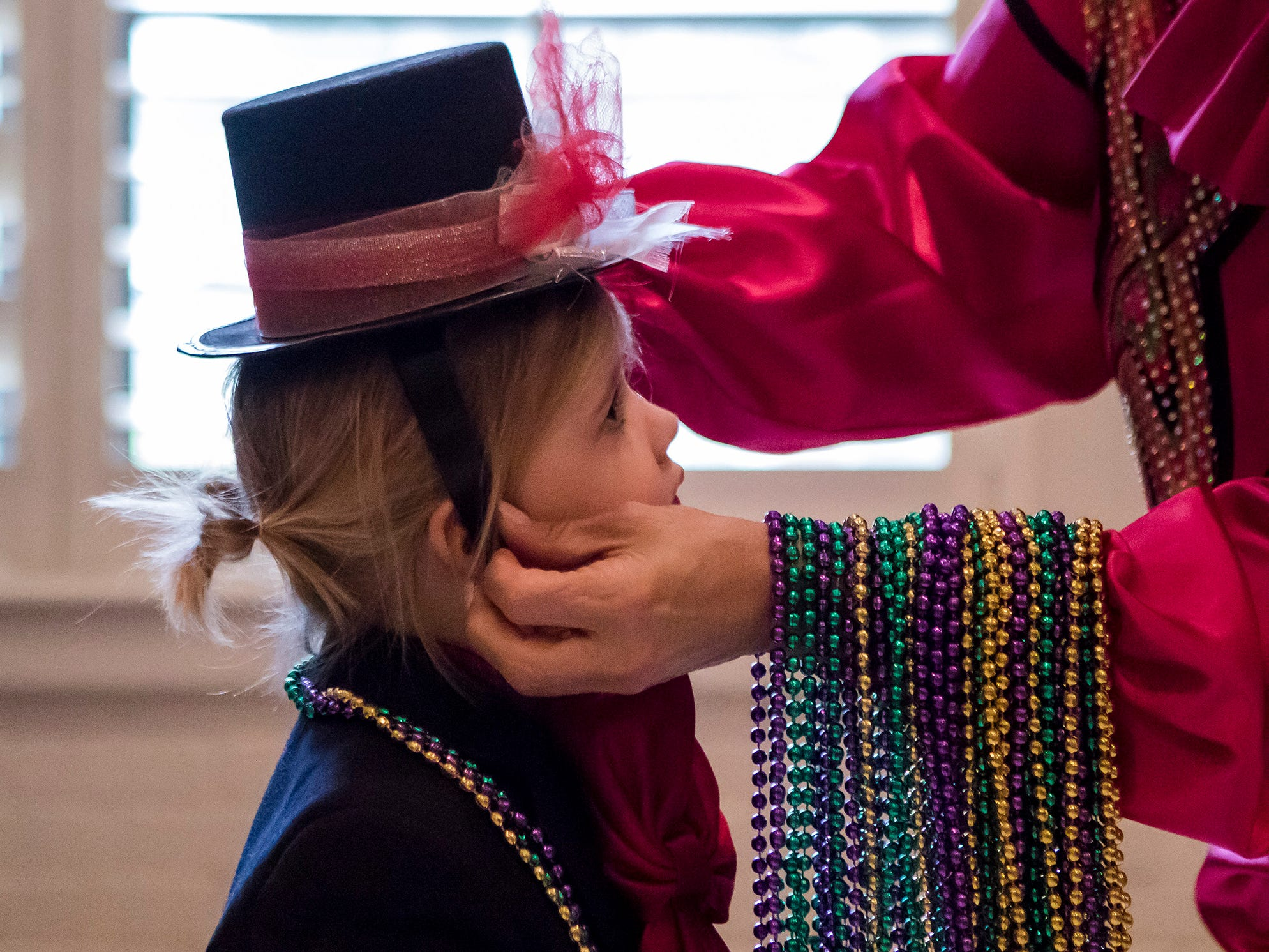 Denise Duplechin fixes Kateri Simon's, 3, hair after her hat fell off during the Krewe of Munchkins parade at St. Paul's Day School in Monroe, La. on Feb. 11.