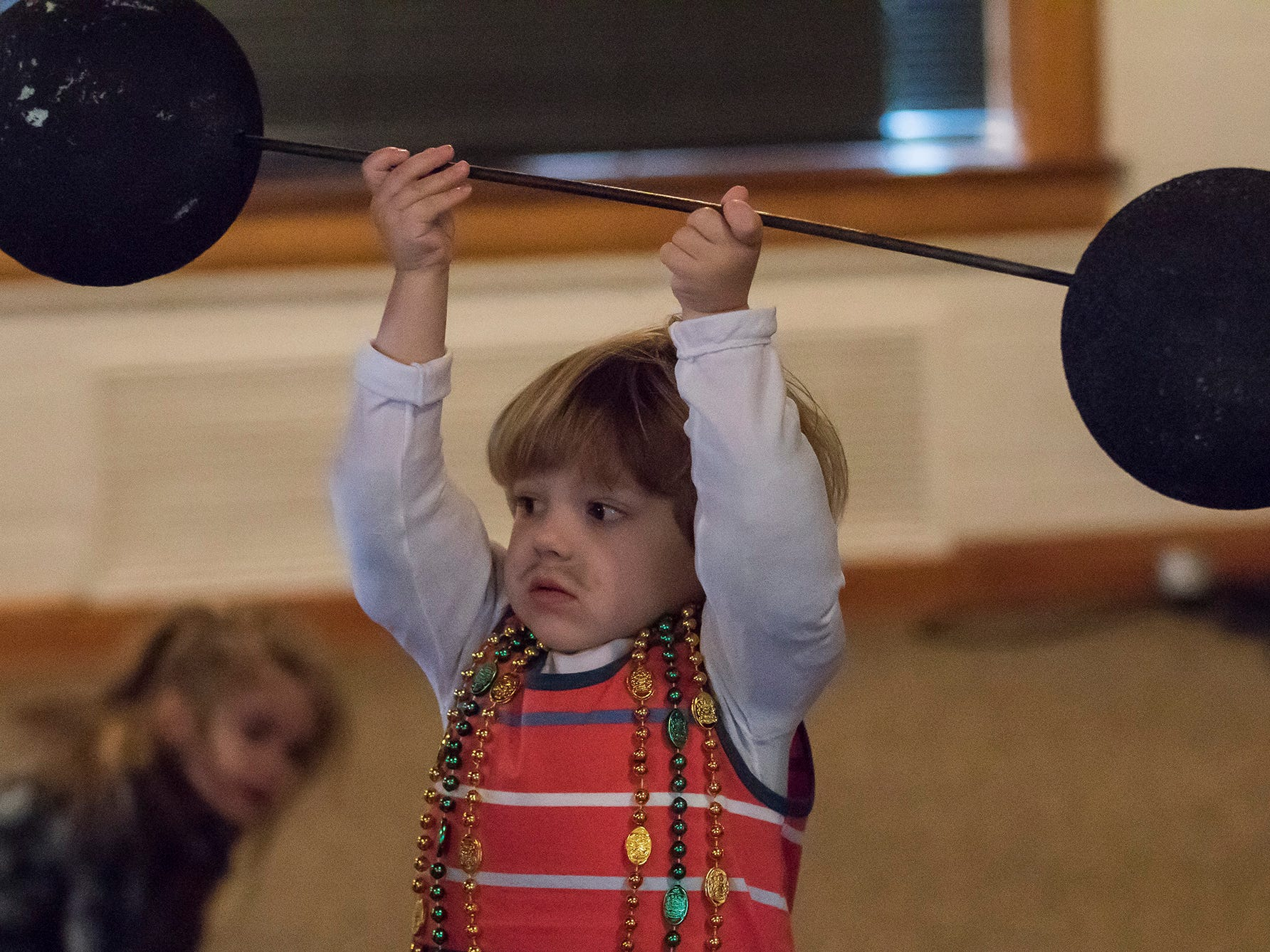 Dressed as a stongman Mason Boyd, 3, lifts his barbell over his head as he waits to partake in the Krewe of Munchkins parade at St. Paul's Day School in Monroe, La. on Feb. 11.