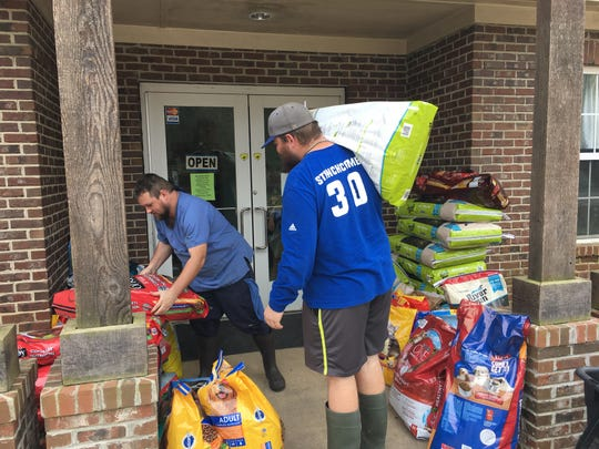 Shelter employees Justin Guillot, left and Caleb Stinchcomb carry donated dog food to storage.