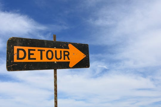 Bold black and orange detour sign with wispy clouds in summer sky background.