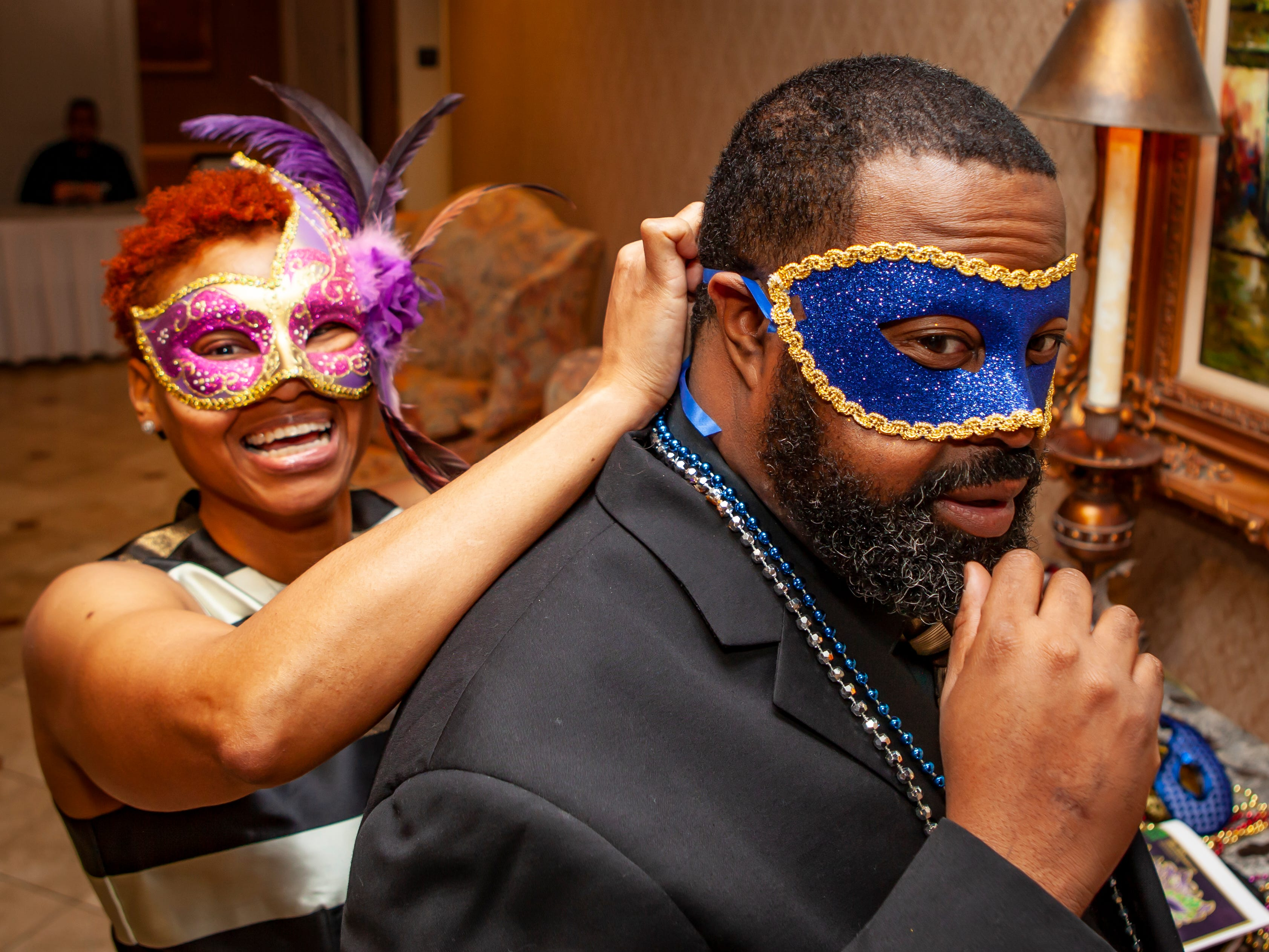 Brandes and Jamil Moore pick out masks at the Omega Psi Phi Mardi Gras party held Saturday, Feb. 9, 2018 at Stones River Country Club in Murfreesboro.