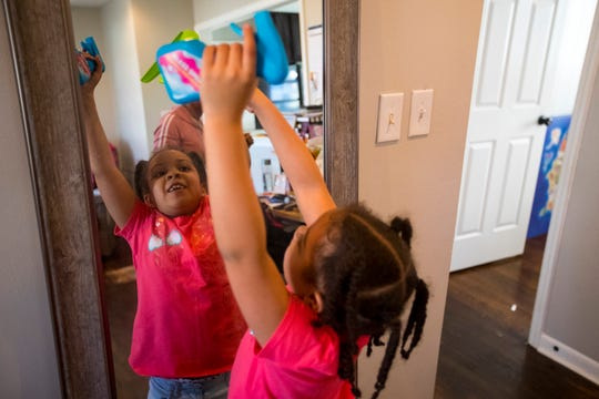 Chloe Rucker, 6, helps her mom, Chelsea Rucker, clean their home in Nashville on Saturday, Feb. 9, 2019.