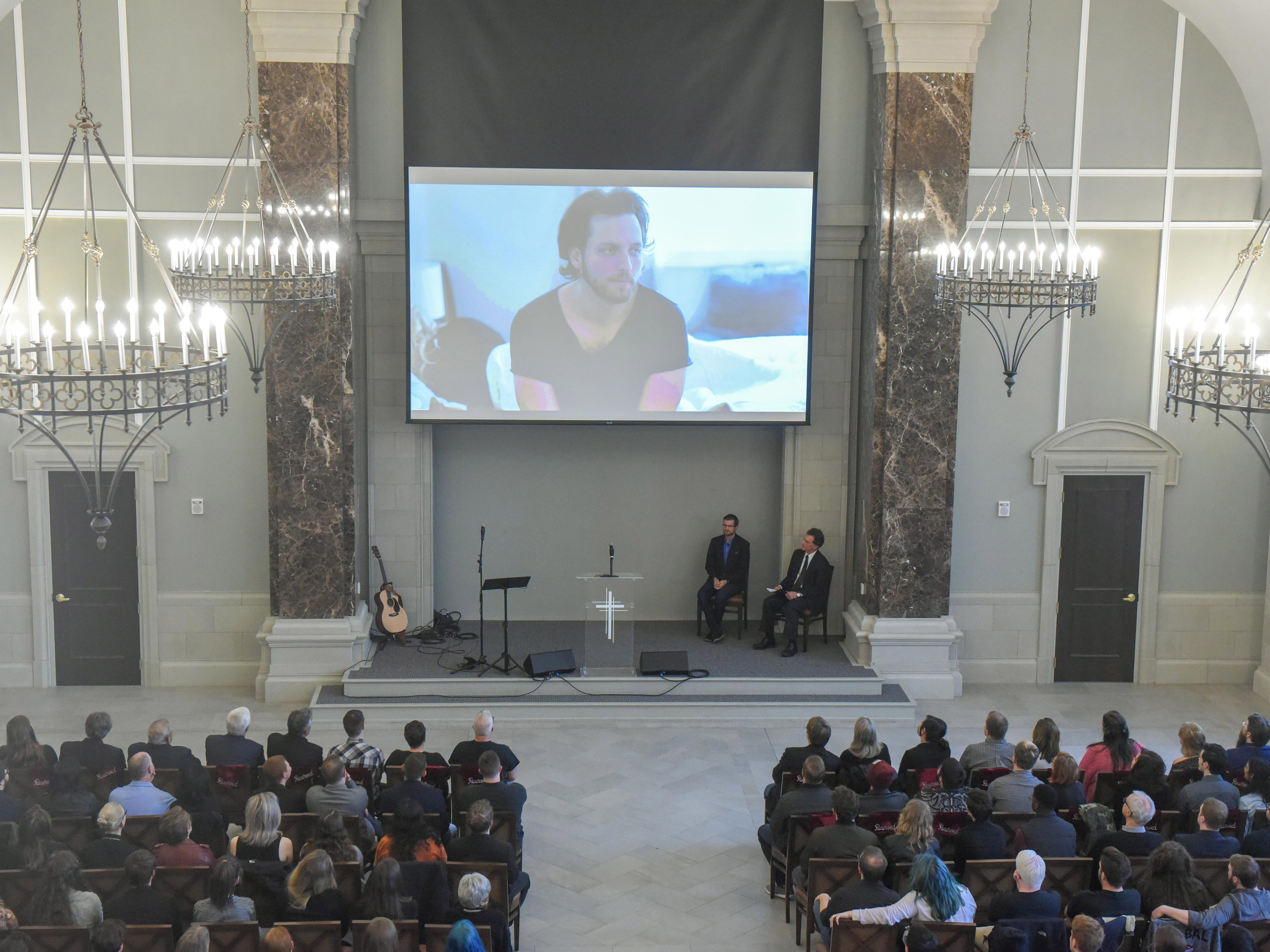 A slideshow plays during a memorial service for Kyle Yorlets at Belmont University in Nashville, Tenn., February 11, 2019.