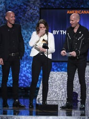 """Phil Hanseroth, from left, Brandi Carlile and Tim Hanseroth accept the award for best Americana album for """"By the Way, I Forgive You"""" at the Grammy Awards on Feb. 10,"""