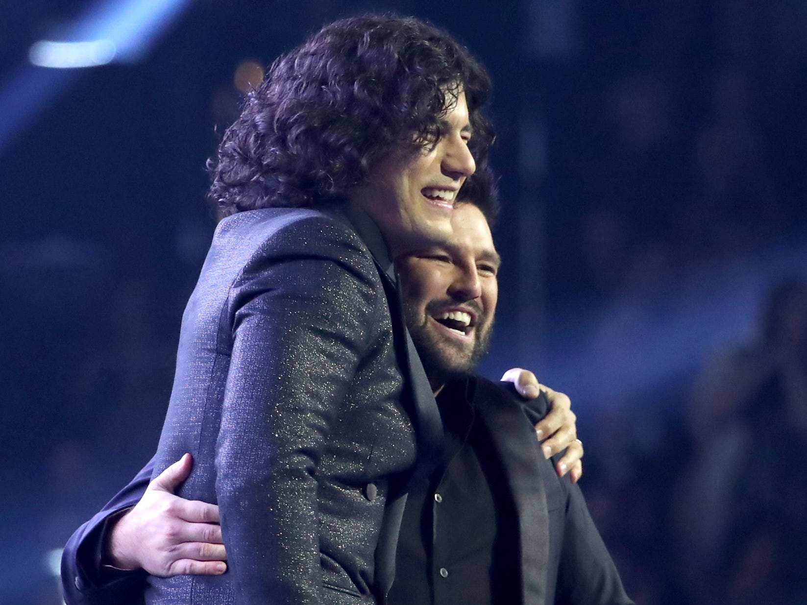 "Dan Smyers, left, and Shay Mooney, of Dan + Shay, embrace after performing ""Tequila"" at the 61st annual Grammy Awards on Sunday, Feb. 10, 2019, in Los Angeles."