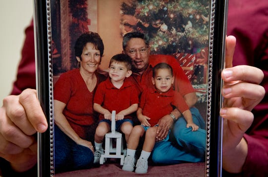 Zach Cruz holds a photo of himself, at right, with his adoptive parents, Lynda and Roger Cruz, and brother, Nikolas. Roger died of a heart attack in 2004, and Lynda died of pneumonia in 2017.