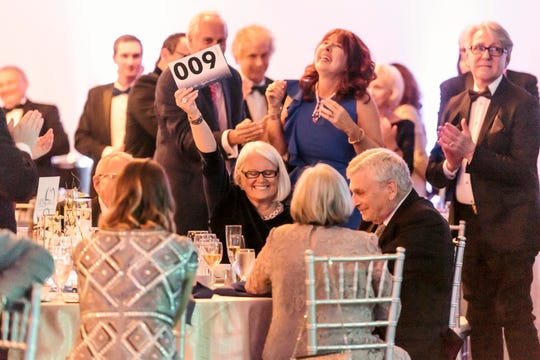 Patty Baker holds up her bidding card as she and her husband take turns bidding up their donation to Naples Players to $1 million on Friday, Feb. 8, 2019.