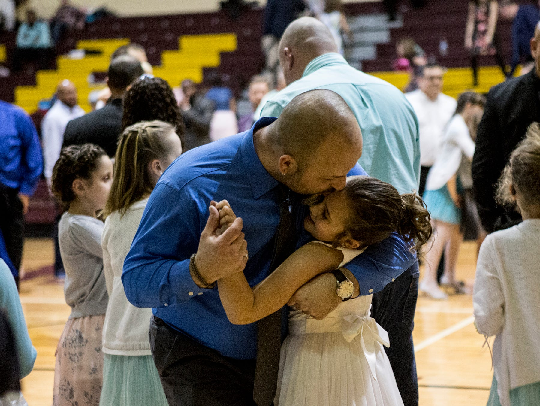 Tim Williams leans over and kisses his daughter, Hanna, 7, during the Daddy/Daughter dance Saturday. The dance was hosted by the Licking County Family YMCA Western Branch. The event, which is a fundraiser for the YMCA, brought in more than 800 people.