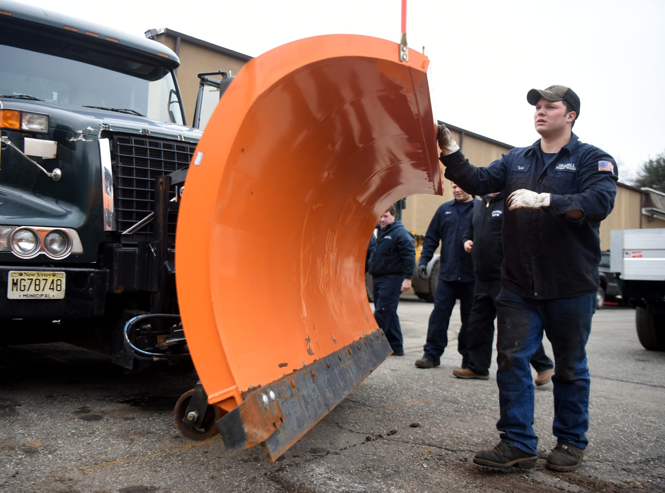 Borough of Oradell Department of Public Works employees including Tyler Coss y Leon, far right, make sure a snow plow is properly attached to a truck on Monday, February 11, 2019 in preparation for a winter storm that could bring snow, ice and freezing rain on Tuesday.