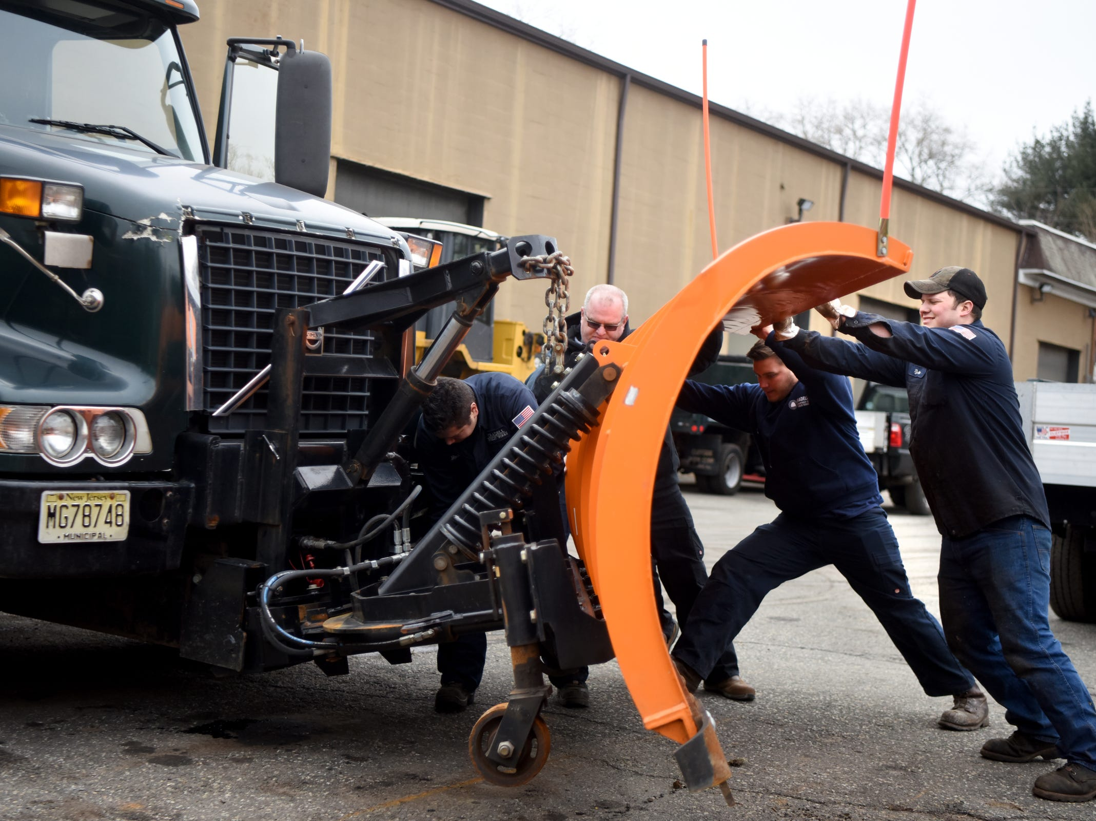 Borough of Oradell Department of Public Works Superintendent Dan Nywening, second from left, and DPW employees, from left, Ross Rhein, Gordon Kohles and Tyler Coss y Leon attach a snow plow to a truck on Monday, February 11, 2019 in preparation for a winter storm that could bring snow, ice and freezing rain on Tuesday.