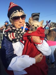 Maria Telles, of Las Cruces, and her dog, Penny, attend a Donald Trump rally outside of the El Paso County Coliseum on Monday, Feb. 11, 2019.