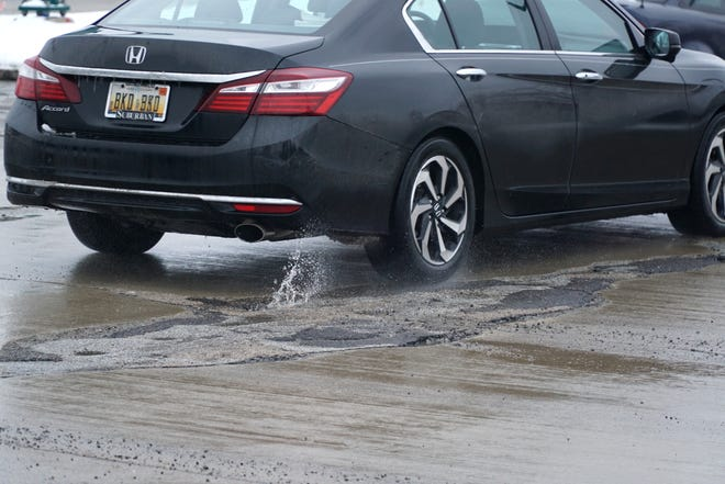 A car kicks up a plume of water after passing over a few potholes at the intersection of Novi Road and Twelve Mile.