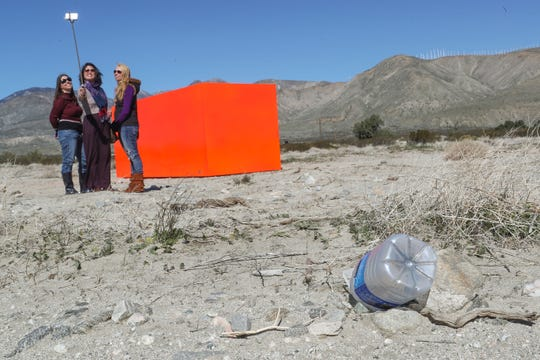 "Art enthusiasts take a selfie at the Desert X art installation ""Specter"" near a discarded plastic bottle.  The exhibit is located at Snow Creek Road and Hwy 111 in Palm Springs. The bottle was there before the group had arrived."