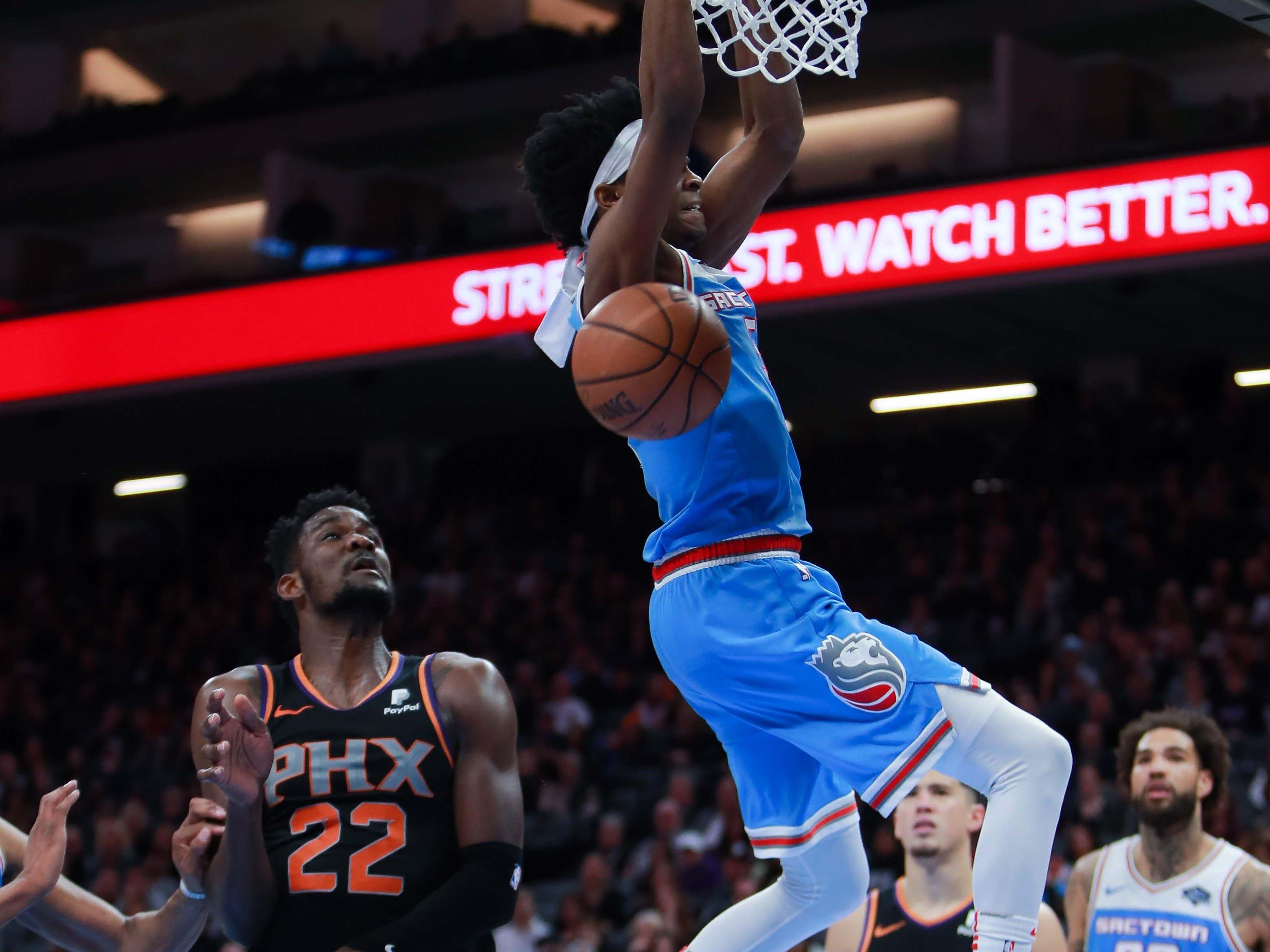 Feb 10, 2019; Sacramento, CA, USA; Sacramento Kings guard De'Aaron Fox (5) dunks the ball against Phoenix Suns center Deandre Ayton (22) during the fourth quarter at Golden 1 Center.