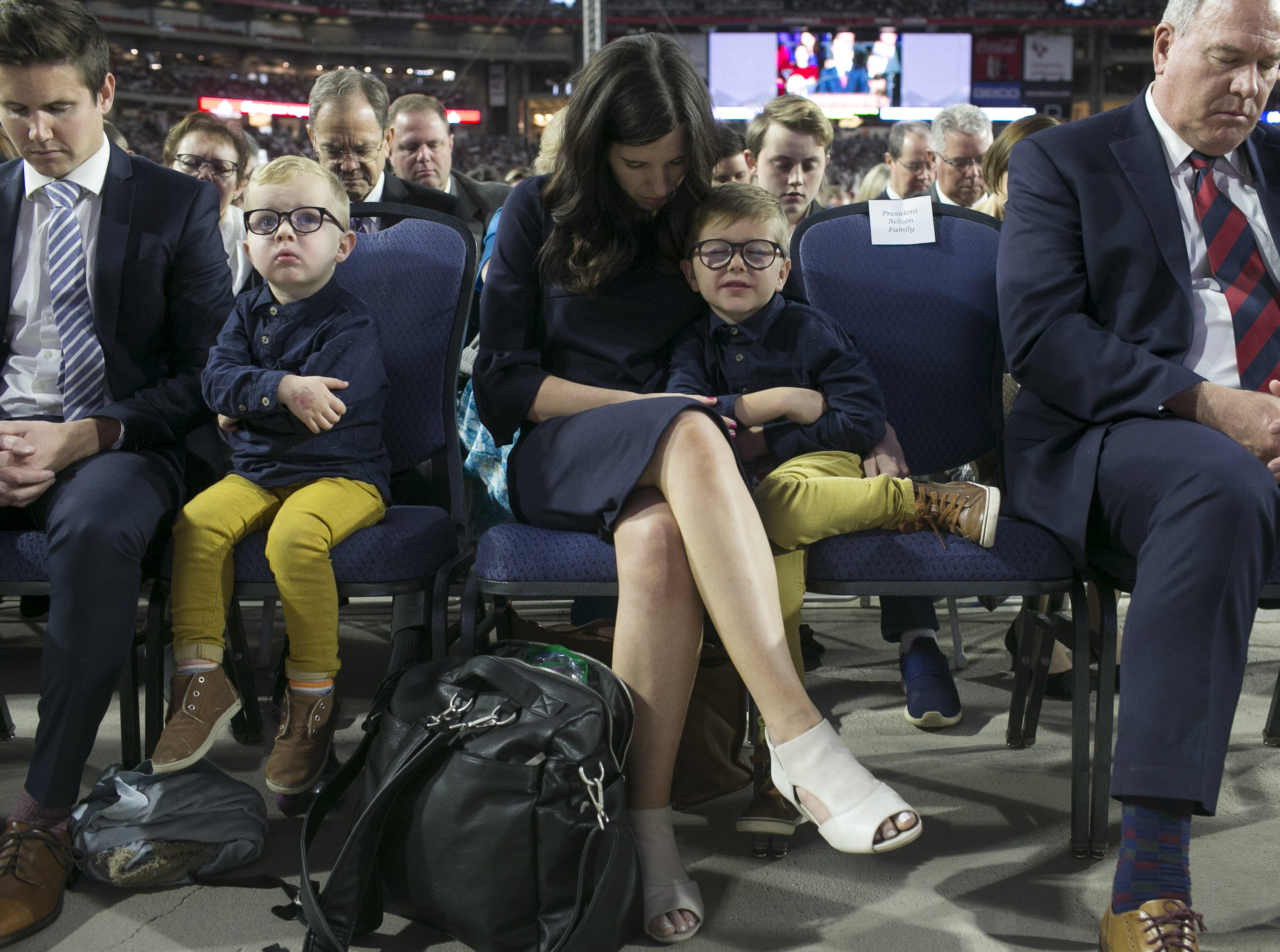 Family of Russell Nelson, president of the Church of Jesus Christ of Latter-day Saints, sit and pray in the front row as Nelson speaks to members of the church at State Farm Stadium on Sunday, Feb. 10, 2019.
