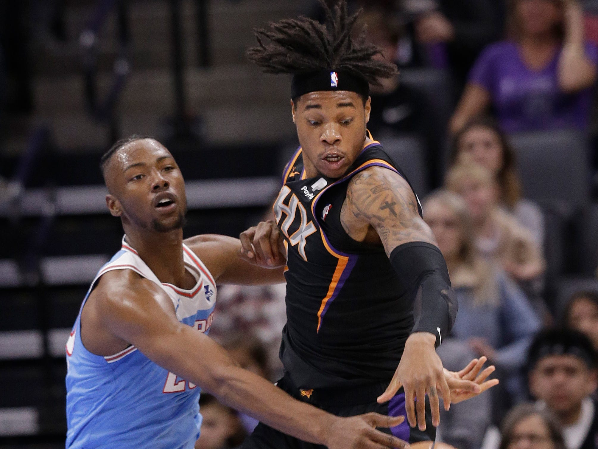 Phoenix Suns forward Richaun Holmes, right, tries to steal a pass intended for Sacramento Kings forward Harry Giles during the first half of an NBA basketball game Sunday, Feb. 10, 2019, in Sacramento, Calif.