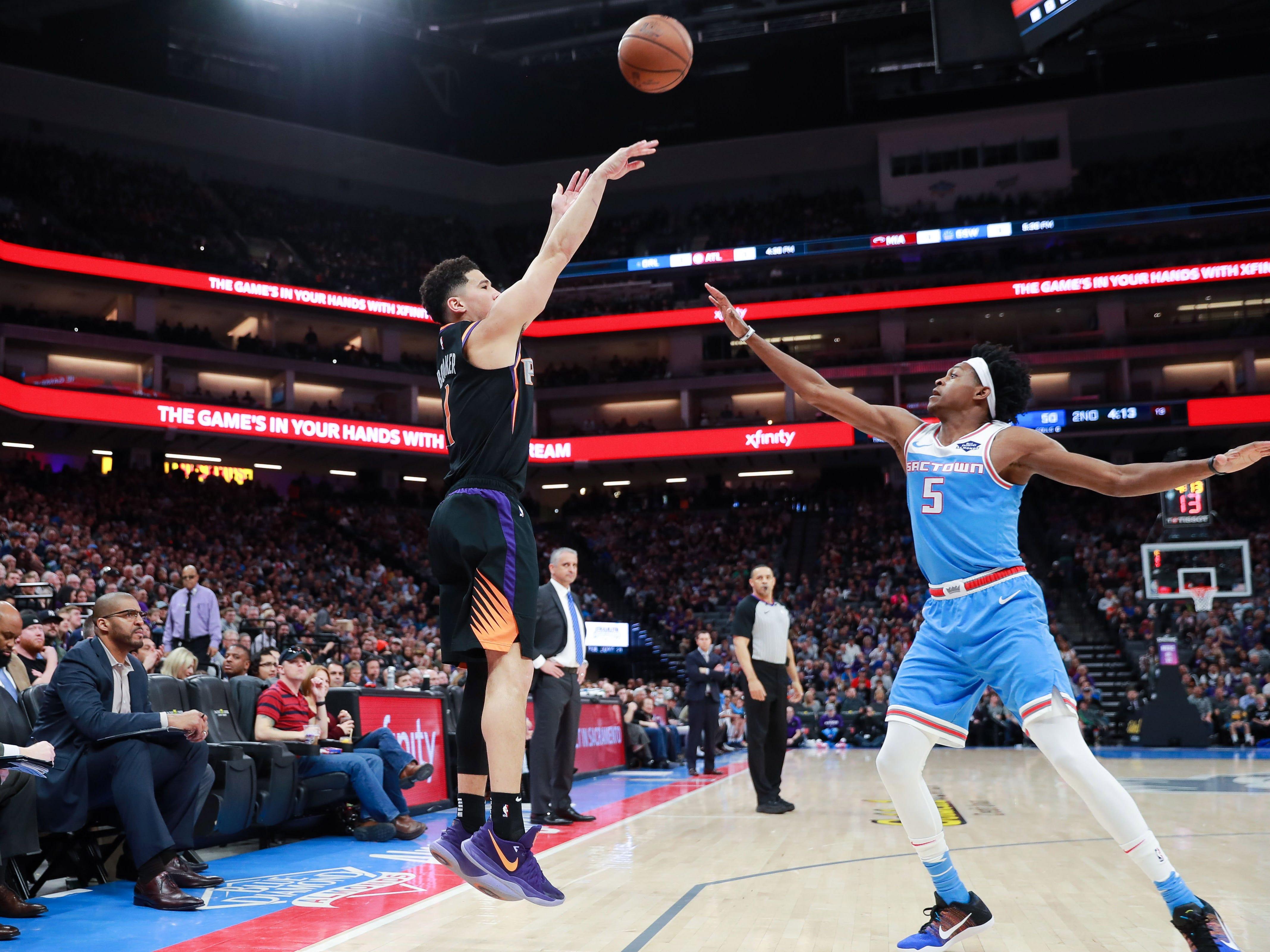 Feb 10, 2019; Sacramento, CA, USA; Phoenix Suns guard Devin Booker (1) shoots the ball over Sacramento Kings guard De'Aaron Fox (5) during the second quarter at Golden 1 Center.